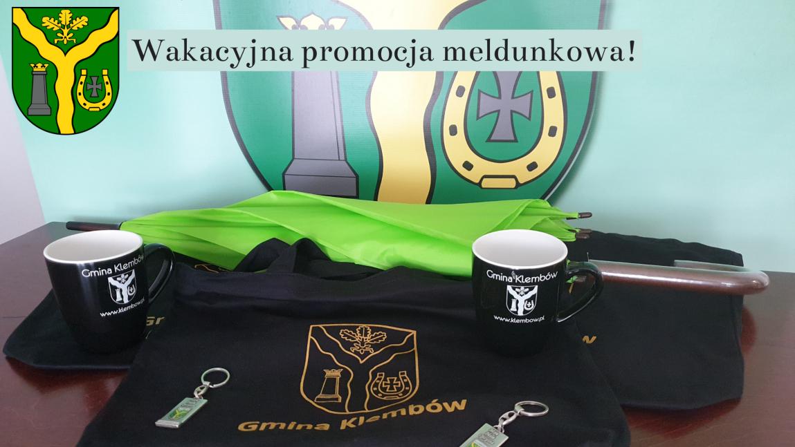 Zdjęcie przedstawia gadżety Gminy Klembów: kubki, parasol, torebki oraz breloczki.