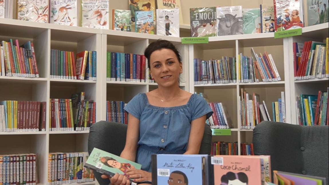 Zdjęcie pracowniczki Biblioteki na tle książek w bibliotece