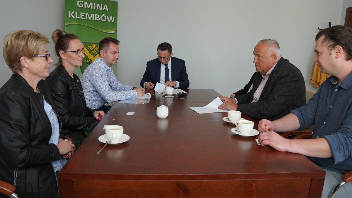 Zdjęcie przedstawia Wójta podpisującego umowę, radnych, oraz wykonawców siedzących razem przy stole..